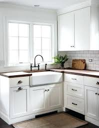 gorgeous cottage kitchen boasts white shaker cabinets fitted with dark nickel vintage cup pulls and butcher