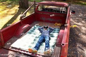 Boy looking through binoculars whilst lying in back of pickup truck ...
