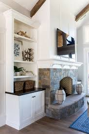 stone base fireplace with white paneling above and white mantel with small corbels fireplace also features built ins on both sides whitepaneling above