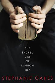 cover for the sacred lies of minnow bly by stephanie oakes two hands hold a