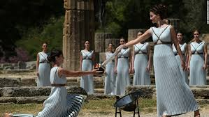 flame lighting olympics. lechou passes the olympic flame into a small ceramic bowl. ceremony was performed at lighting olympics s