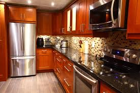 modern luxury kitchen with stainless steel appliances mosaic backsplash black galaxy granite counter tops medium brown cabinetry and small appliances