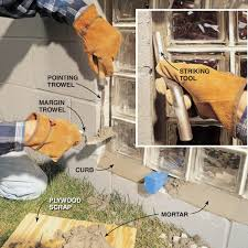 pack mortar into the gaps under and alongside the glass block window panel pack the bottom and smooth the curb first staying away from the wedges