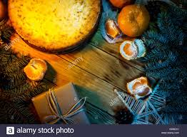 cheese cake against wooden background with oranges gift box and decoration