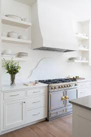 kitchen with solid white open shelves and silver and gold french stove via parkes and lamb