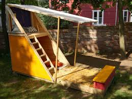 a playhouse with stairs a bench and a fold down roof