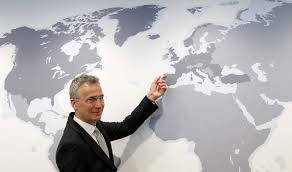 NATO Secretary-General Jens Stoltenberg poses next to a world map during the first day in the new NATO headquarters building in Brussels, Belgium, Reuters/UNI - APN Live