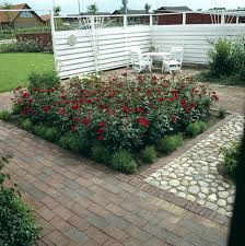 red roses in bed beside pebbled area in garden with white chairs on patio screened by tall white fence
