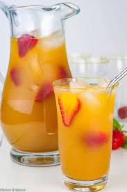 a pitcher and a glass of peach ginger iced green tea garnished with strawberries