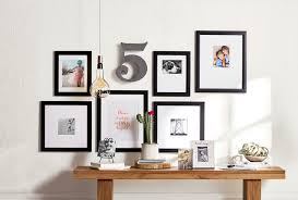 photos are in black frames arranged on a wall