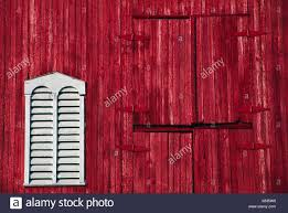 red and white barn doors. Red Barn Door And White Louvered Window - Stock Image Doors