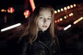 teenage girl wearing leather jacket at night
