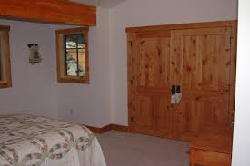 classic pine wooden unfinished closet door with king size bed also single glass window in vintage cottage bedroom
