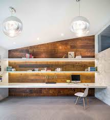 gorgeously lit shelves and reclaimed wood wall create a stunning midcentury modern home office from