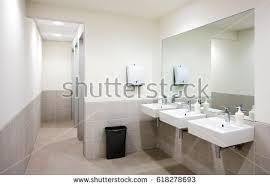 public bathroom mirror. empty public bathroom with white sinks and wide wall mirror, air hand drier black mirror r
