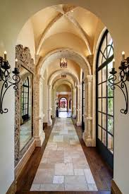 beautiful hallway with travertine and wood floors lots of outdoor light and arched ceilings