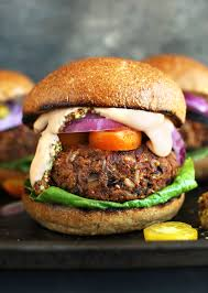 an amazing grillable veggie burger patty on a bun with lettuce tomato onion and