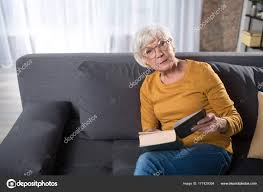 reading time waist up portrait of thoughtful woman looking at camera while holding book she is resting at sitting room on couch