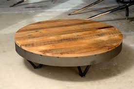 round light brown wooden coffee table with short triangle black steel legs placed on the cream