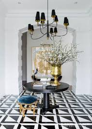 an arched doorway leads to a gorgeous black and white foyer is illuminated by a farlane large chandelier hung over a round black pedestal table placed on