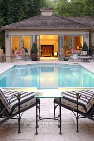 pool house ideas. View Of A Lighted Pool House Next To An Inground Swimming Pool, With Two Loungers Ideas