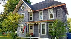 painting exterior trim. blue victorian house exterior with cream and coral trim painting