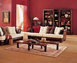 simple living room design with brown white sofa wooden coffee table red wall paint and wooden storage and white rug image