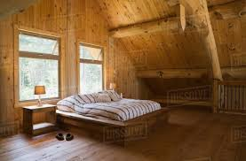 King size bed with wooden bed frame in the master bedroom, on mezzanine inside a handcrafted Eastern white pine cottage style log home, Quebec, Canada ...