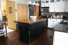 large kitchen with island orange acrylic dome ceiling lamp exquisite dark wooden dining table sleek brown granite countertop simple light gray kitchen