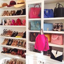 chic walk in closet features a built in cabinet with glass doors filled with designer bags next to shelves for shoes