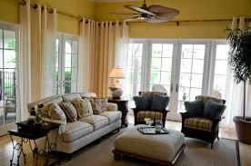 This casual living room and sunroom has bamboo curtain rods that extend  around the perimeter of