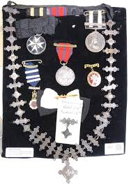 st john s ambulance hallmarked silver chain with 26 year labels and 16 pendants