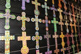 small painted crosses hang on a wall