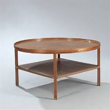 circular coffee table with underlying square shelf by kaare klint