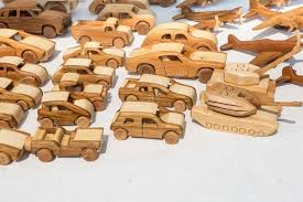 a selection of wooden toy cars tanks and planes photo by kyrien