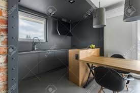 Gray Kitchen In Industrial Style With Wooden Table And Black Stock