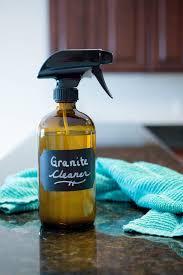 an amber glass spray bottle of homemade granite cleaner on a dark granite counter