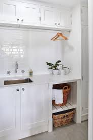 cabinets and tension rod drying rack over laundry sink