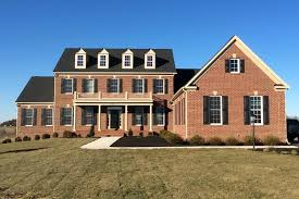 Brick Front Of House On The Plains With A 3 Window Balcony, Dark Shingles,