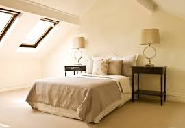 attic master bedroom. dark nightstands highlight a neutral color palette and the angle of ceiling rises sharply in attic master bedroom