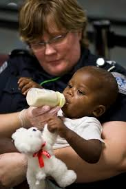 a cbp officer feeds one of the orphans transported from haiti to orlando sanford international airport cbp officer job description