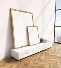 two blank frames on white floor shelf white wall window to the