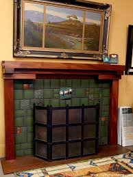 arts and crafts tiles surround a fireplace with a greene u0026 greene style wood mantle