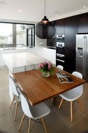 black table top kitchen. a black kitchen with white marble island and an additional tabletop for having meals table top