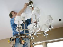 electrician installing high end designer chandelier in home addition