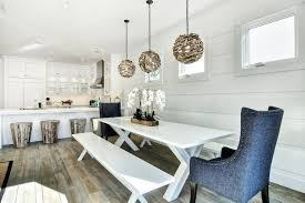 cottage dining room features white horizontal paneled walls framing three small square windows illuminated by three round driftwood chandeliers hanging over