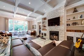 stackable stone fireplace with built ins on each side for traditional family room and tray ceiling