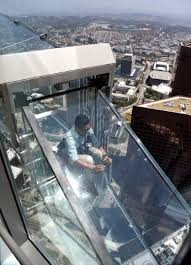 a member of the media rides the skyslide from the 70th to 69th floor of the