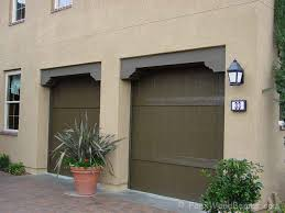 faux wood l header combined with fake wood corbels decorate a garage door opening nicely