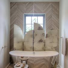 tub nook with herringbone tiled accent wall